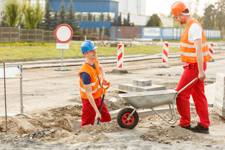 road worker: Image of worker with wheelbarrow on road construction Stock Photo