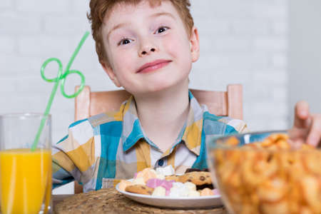 junky: Happy little boy eating plate of sweets an drinking orange juice for dessert Stock Photo