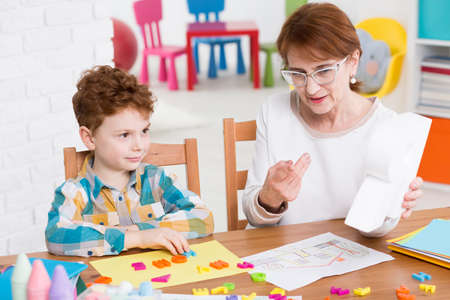 color therapist: Little boy during lesson with his speech therapist. Learning through fun and play Stock Photo