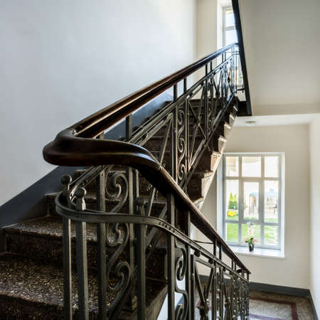 stairs: Staircase with old, decorative railing and white walls
