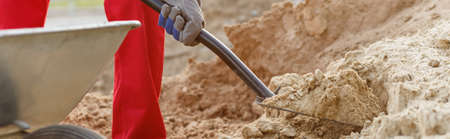 digging: Panorama of manual worker with shovel digging ground