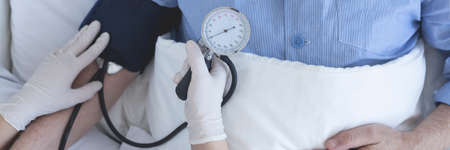 hospice: Close up of a nurse taking patients blood pressure