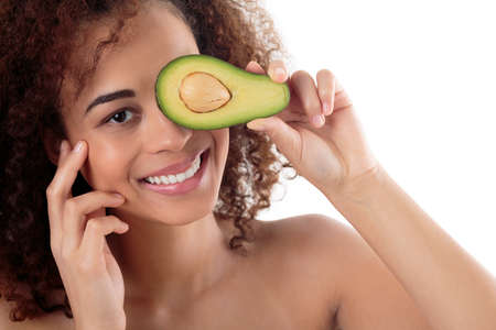 one woman: Portrait of an afroamerican woman covering one eye with a piece of an avocado, white background