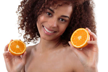 afroamerican: Afroamerican woman holding two pieces of an orange, smiling, white background