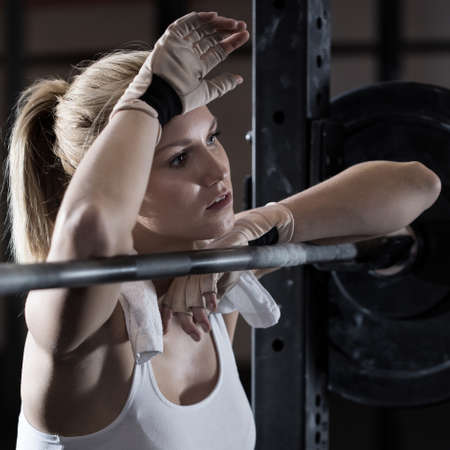 exhausted: Young pretty girl tired after weightlifting at gym Stock Photo