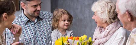 matrimonio joven con pequeñas hijas abuelos visitar durante la cena familiar