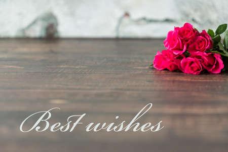 """Colpo di un tavolo con un mazzo di rose rosa e una scritta """"Auguri"""""""