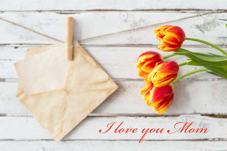 old envelope: Shot of a bunch of tulips, an old envelope and a writing I love you mum
