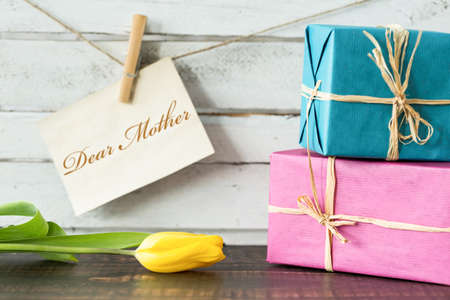 my dear: Shot of two gifts, a yellow tulip and a card saying Dear Mother Stock Photo