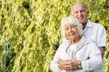 tenderly: Senior marriage is cuddling tenderly in park