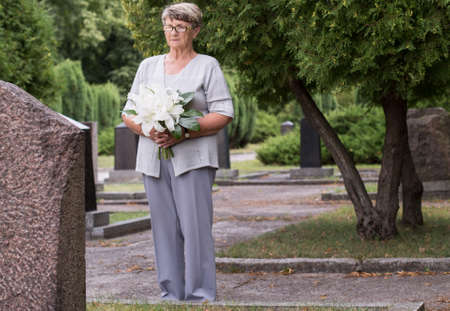 graves: Elderly woman dressed in gray standing in front of a grave in a cemetery, holding a bunch of flowers