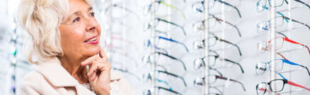 shortsightedness: Senior optician client is choosing prescription glasses
