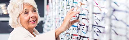 expositor: Mujer en busca de nuevos vasos en una tienda de gafas Foto de archivo