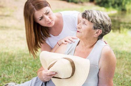 Shot van een oude dame zittend op het gras op een zonnige dag, gevoel van zwakte, en een jonge vrouw te helpen haar