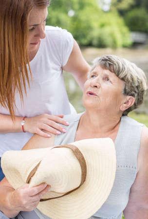 Disparo de una mujer mayor explotación de un sombrero para el sol, sensación de desmayo, y una mujer joven la asistencia a