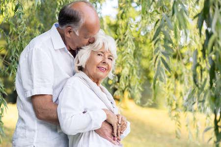 matrimonio feliz: Madurar matrimonio feliz abrazando cariñosamente en el parque Foto de archivo