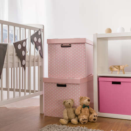 Photo of white cot and pink boxes in child bedroom