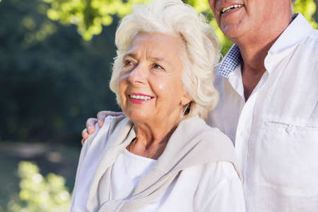 embraced: Smiling elderly woman embraced by husband in park Stock Photo