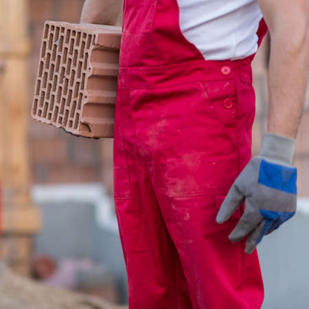 protective gloves: Close-up of a construction worker in red overalls and protective gloves holding a brick block