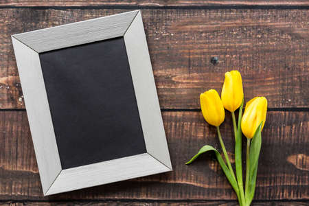 rustical: Light frame and bouquet of yellow tulips lying on rustical, wooden board