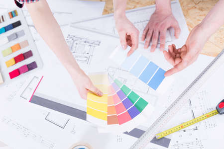 Close-up of womans hands holding paint colour samplers over a drawing table filled with technical drawings