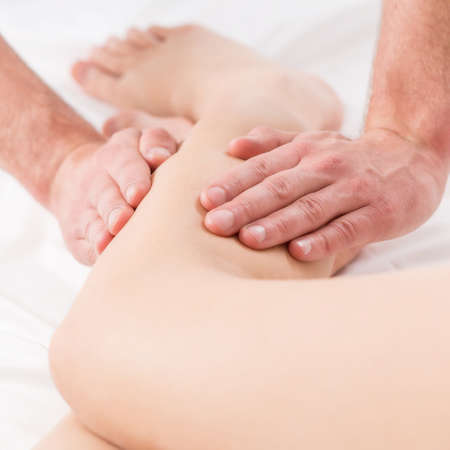 color therapy: Close-up of male physiotherapist doing legs massage Stock Photo