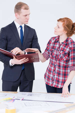 drawing table: Shot of a young, red-haired woman discussing some documents with a smartly dressed man, standing beside a drawing table filled with plans Stock Photo