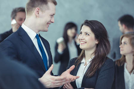 young entrepreneurs: Portrait of two young entrepreneurs chatting lively in a blurred crowd of people Stock Photo