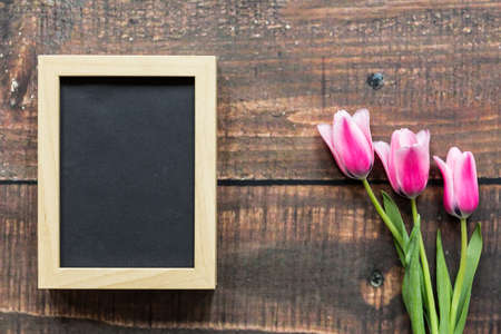 rustical: Three pink tulips and empty frame lying on rustical, wooden planks Stock Photo