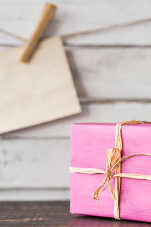 rustical: Wrapped pink present and card hanging on a string, rustical planks in the background Stock Photo