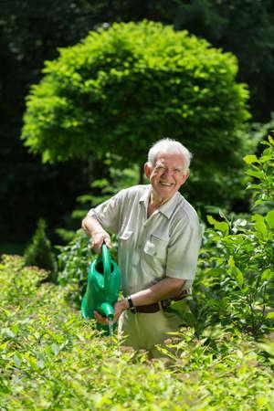 hombres trabajando: Jardinero con una regadera el cuidado de las plantas
