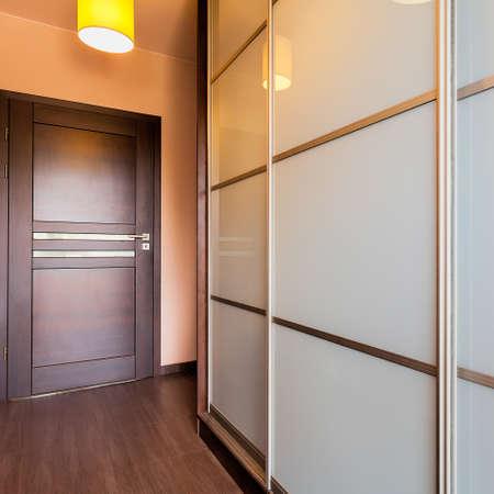 urban apartment: Urban apartment - brown corridor with white wardrobe
