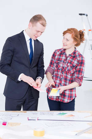 smartly: Young woman discussing sample paint colours with a smartly dressed man inside a room that is being renovated