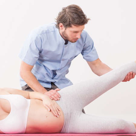 birthing: Pregnant woman exercising her legs with physiotherapist Stock Photo