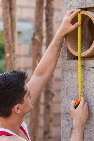 diameter: Close-up of a young builder measuring a pipe diameter in a bulding site
