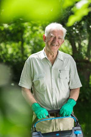 hobbyist: Senior man with a lawnmower in the garden Stock Photo