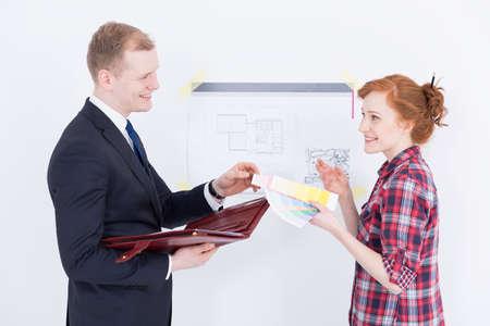 dibujo tecnico: Mujer joven que sostiene una muestra de color de pintura que habla con un hombre vestido elegantemente con un maletín, al lado de una pared con el dibujo técnico en ella Foto de archivo