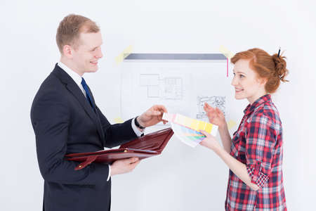 technical drawing: Young woman holding a paint colour sampler talking to a smartly-dressed man with a briefcase, beside a wall with technical drawing on it