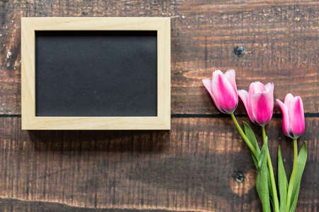 rustical: Three pink tulips and empty wooden frame lying on rustical planks