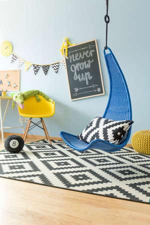 azul marino: , Sitio del adolescente brillante moderno con la silla azul marino que cuelga y la alfombra estampada