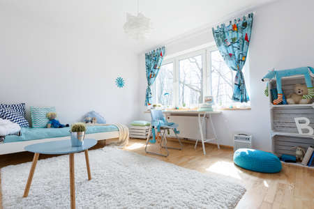 Very spacious and light child room with large window, filled with white and blue decorative elements