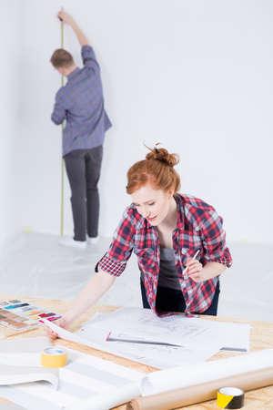 dibujo tecnico: Joven pareja haciendo el trabajo de decoración de interiores dentro de una habitación que está siendo renovado Foto de archivo