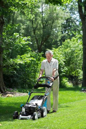 hobbyist: Man working in the garden using a lawnmower