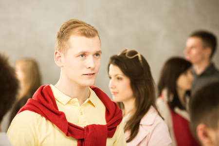 casually dressed: Portrait of a young red-haired, casually dressed man among a crowd of people