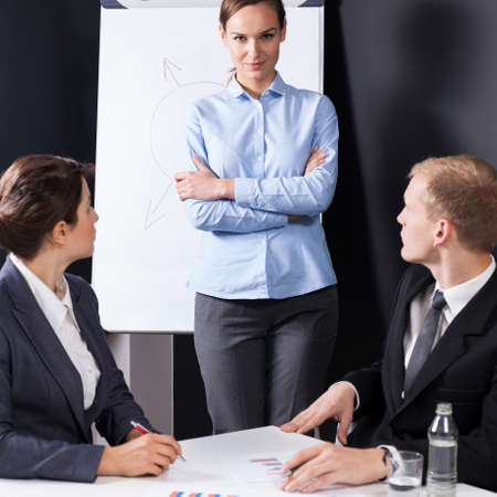 bossy: Young pretty bossy businesswoman talking with her colleagues Stock Photo