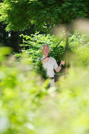 hobbyist: Smiling hobbyist senior gardener cultivating the garden