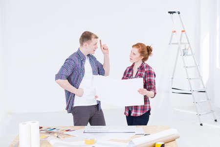 dibujo tecnico: hombre y una mujer en ropa de trabajo discutiendo un dibujo técnico dentro de una habitación en proceso de renovación