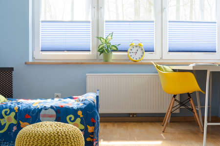 radiator: Fragment of a child room with large blinded window, radiator underneath, covered bed and desk with chair beside it