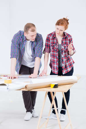 drawing table: Shot of man and woman discussing something beside a drawing table full of technical drawings and rolls of paper
