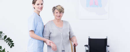 geriatrician: Older disabled woman with walking stick and her pretty young caregiver in a duster helping patient to walk
